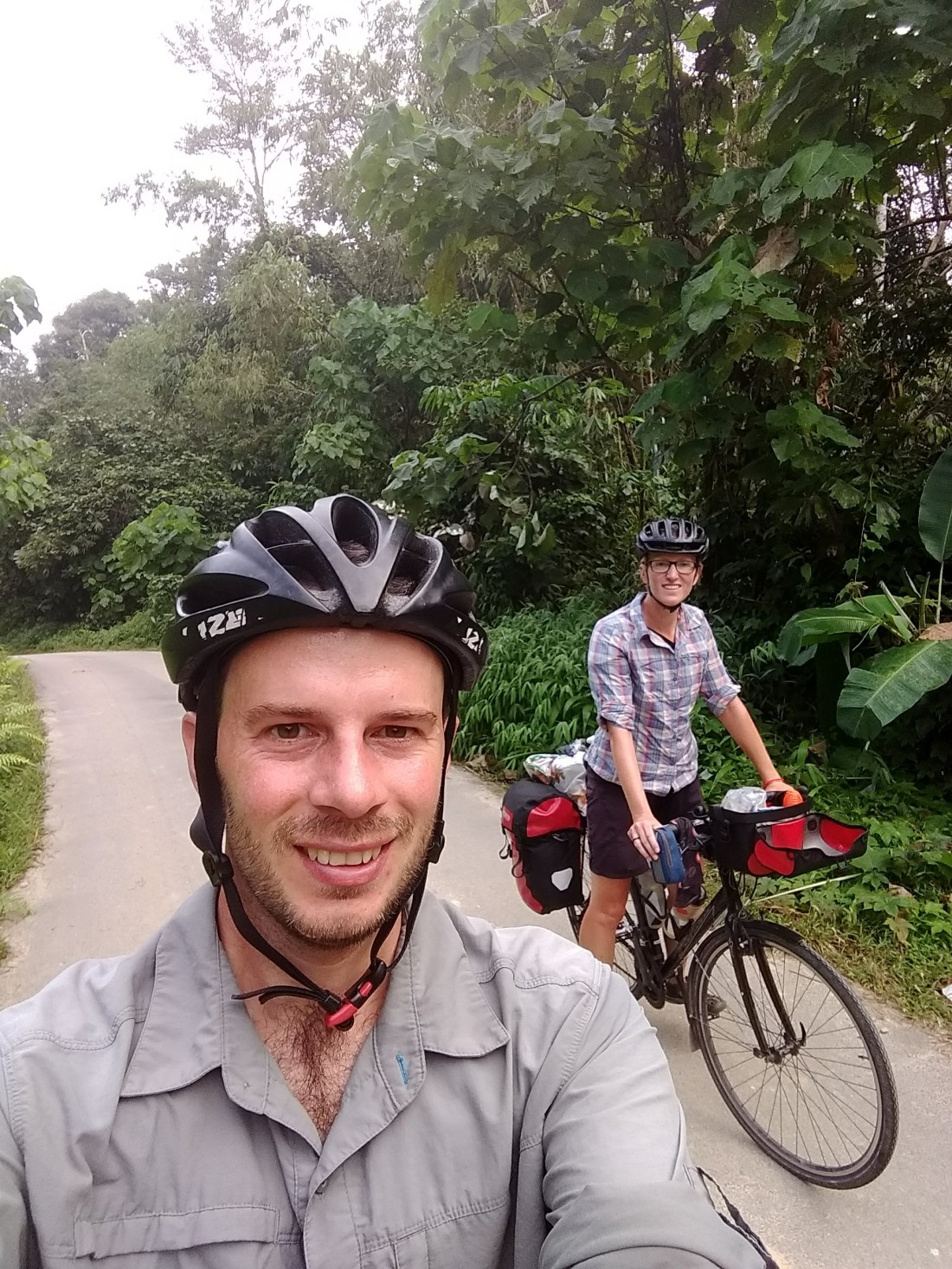 Man and woman on bikes, surrounded by tropical foliage